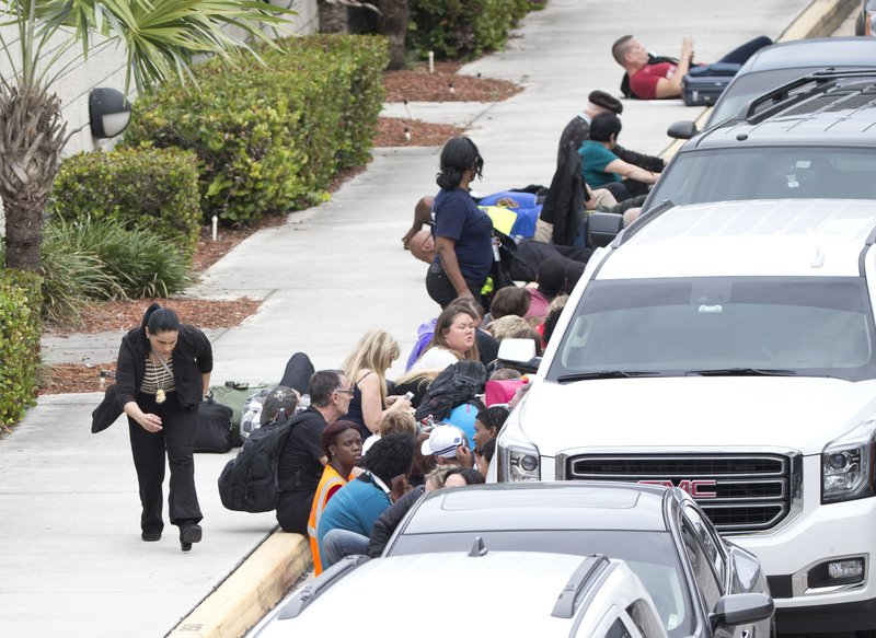 <p>FILE - In this Jan. 6, 2017, file photo, people take cover behind vehicles at Fort Lauderdale–Hollywood International Airport, in Fort Lauderdale, Fla. 2017 in Florida began with tragedy and violence. On Jan. 6 Esteban Santiago flew from Alaska to Fort Lauderdale-Hollywood International Airport, walked into the baggage retrieval area and opened fire, killing five people and wounding six and sending thousands into panic. (AP Photo/Wilfredo Lee, File)</p>