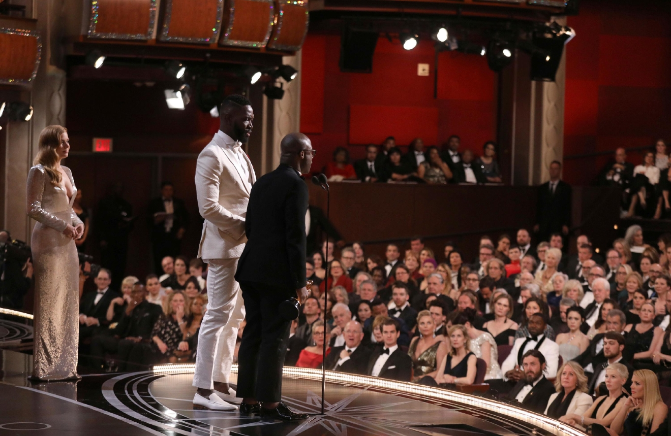 "Tarell Alvin McCraney, center, and Barry Jenkins accept the award for best adapted screenplay for ""Moonlight"" as Amy Adams, left, watches on at the Oscars on Sunday, Feb. 26, 2017, at the Dolby Theatre in Los Angeles. (Photo by Matt Sayles/Invision/AP)"