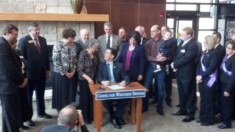 Gov. Scott Walker signs the Silver Alert bill into law in Green Bay, Friday, April 11, 2014. (WLUK/Andrew LaCombe)