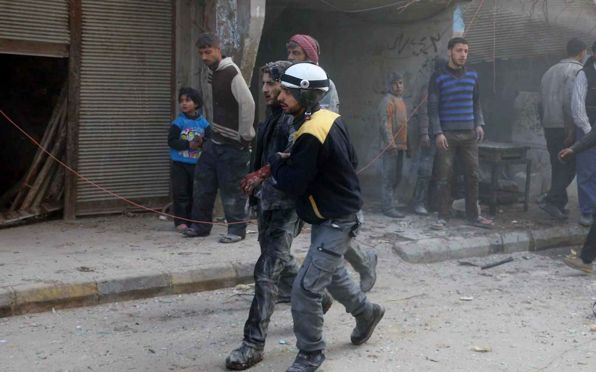 This photo provided by the Syrian Civil Defense White Helmets, which has been authenticated based on its contents and other AP reporting, shows a civil defense worker helping a wounded man after airstrikes hit a rebel-held suburb near Damascus, Syria, Thursday, Feb. 8, 2018. Syrian rescue workers and activists say the death toll from ongoing government strikes on the opposition-held region near the capital Damascus has risen to at least 35. (Syrian Civil Defense White Helmets via AP)