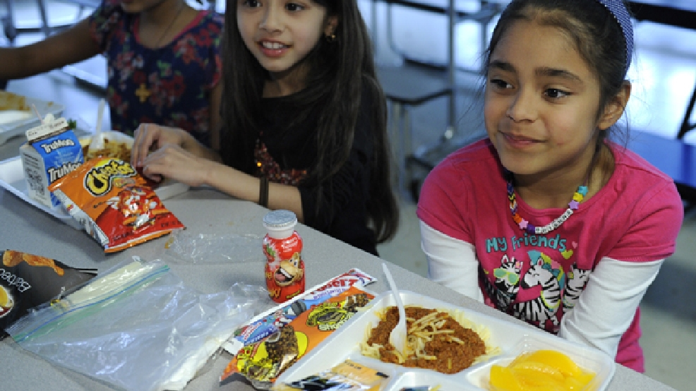 In this Tuesday, April 29, 2014 photo, Brianna Delcid-Gomez, 7, right, Ruth Gebregiorgis, 8, far left, and Amina Sharif, 7, center, eat lunch at the Patrick Henry Elementary School in Alexandria, Va. Starting next school year, pasta and other grain products in schools will have to be whole-grain rich, or more than half whole grain. The requirement is part of a government effort to make school lunches and breakfasts healthier. (AP Photo/Susan Walsh)