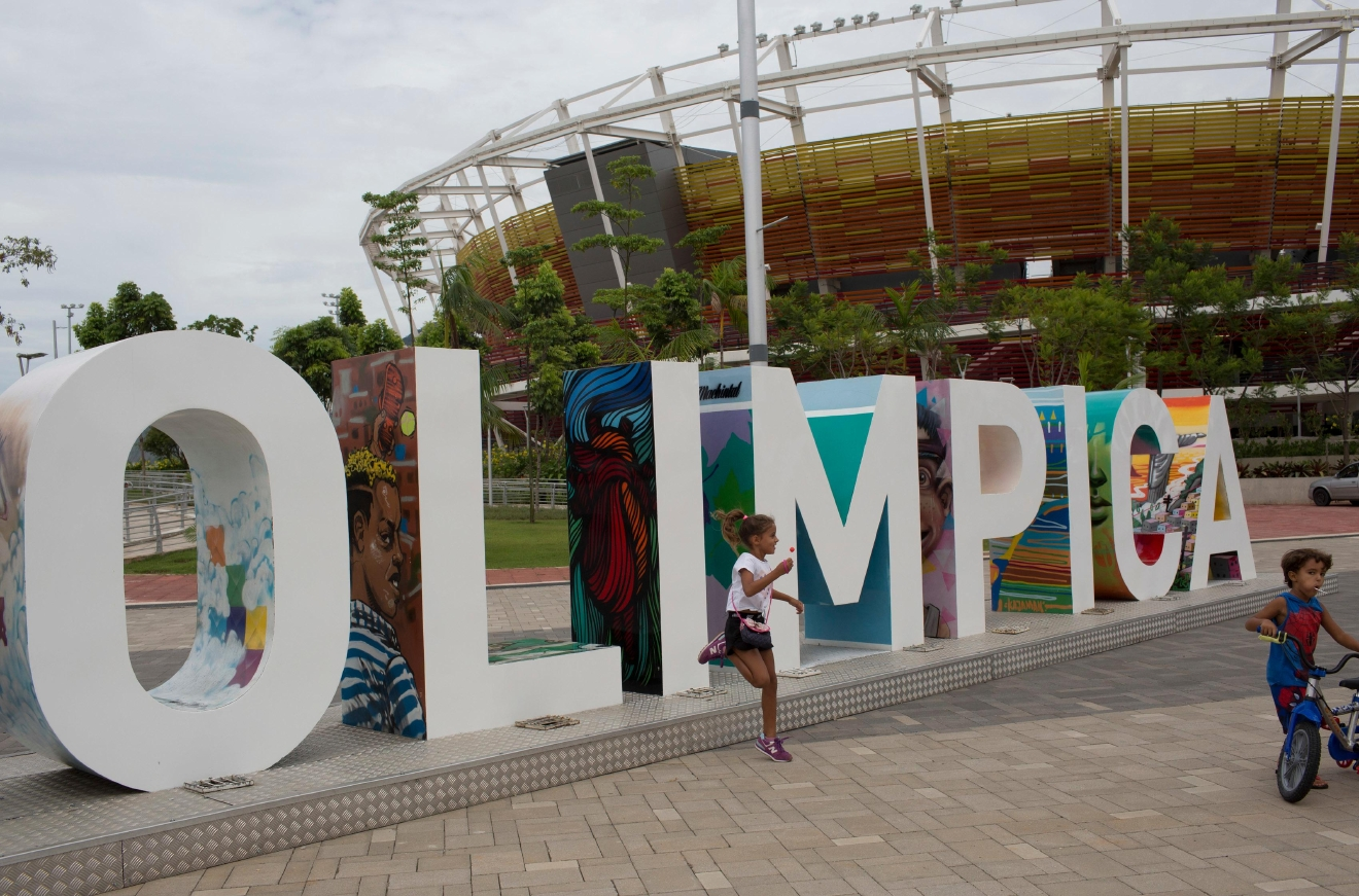 In this Feb.4, 2017 photo, children play near the Olympic Park sign in Rio de Janeiro, Brazil. Rio organizers still owe creditors about $40 million. Four of the new arenas in the main Olympic Park have failed to find a private-sector management, and ownership has passed to the federal government. Another new arena will be run by the cash-strapped city. (AP Photo/Silvia Izquierdo)