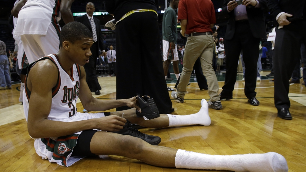 Milwaukee Bucks' Giannis Antetokounmpo signs his shoes after an NBA basketball game against the Atlanta Hawks, Wednesday, April 16, 2014, in Milwaukee. The Bucks lost 111-103. (AP Photo/Morry Gash)