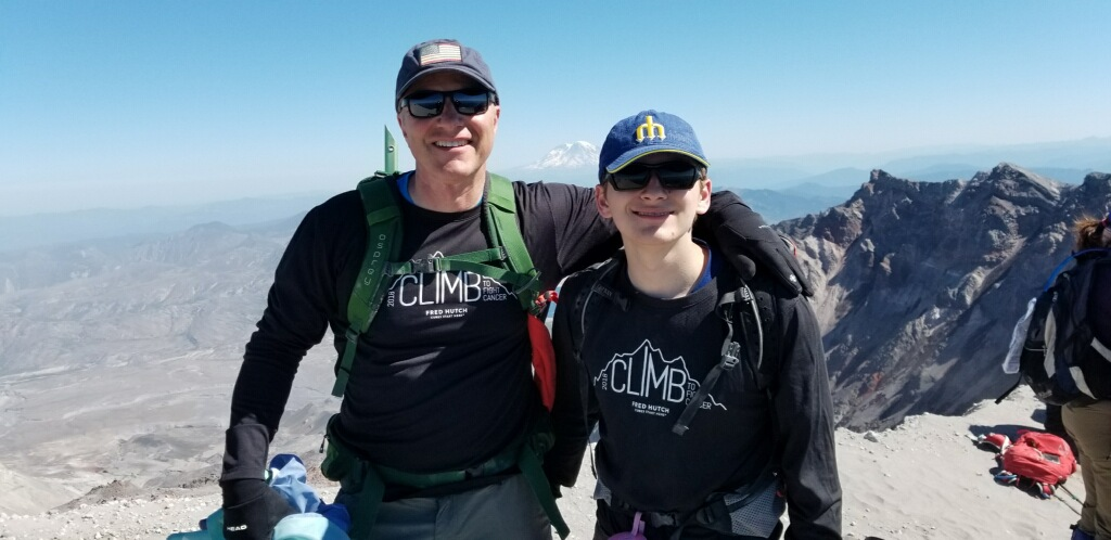 "Standing atop Mt. St. Helens, KVI's John Carlson summits the legendary volcano for the second consecutive year in the Fred Hutchinson Cancer Research Center's ""Climb To Fight Cancer"" fundraiser. In the background is Spirit Lake and beyond is Mt. Rainier. John, his son Drew, guide Chris Burrows and the rest of the climbing team reached the summit on Sunday July 22, 2018. (photo: KVI Staff)."