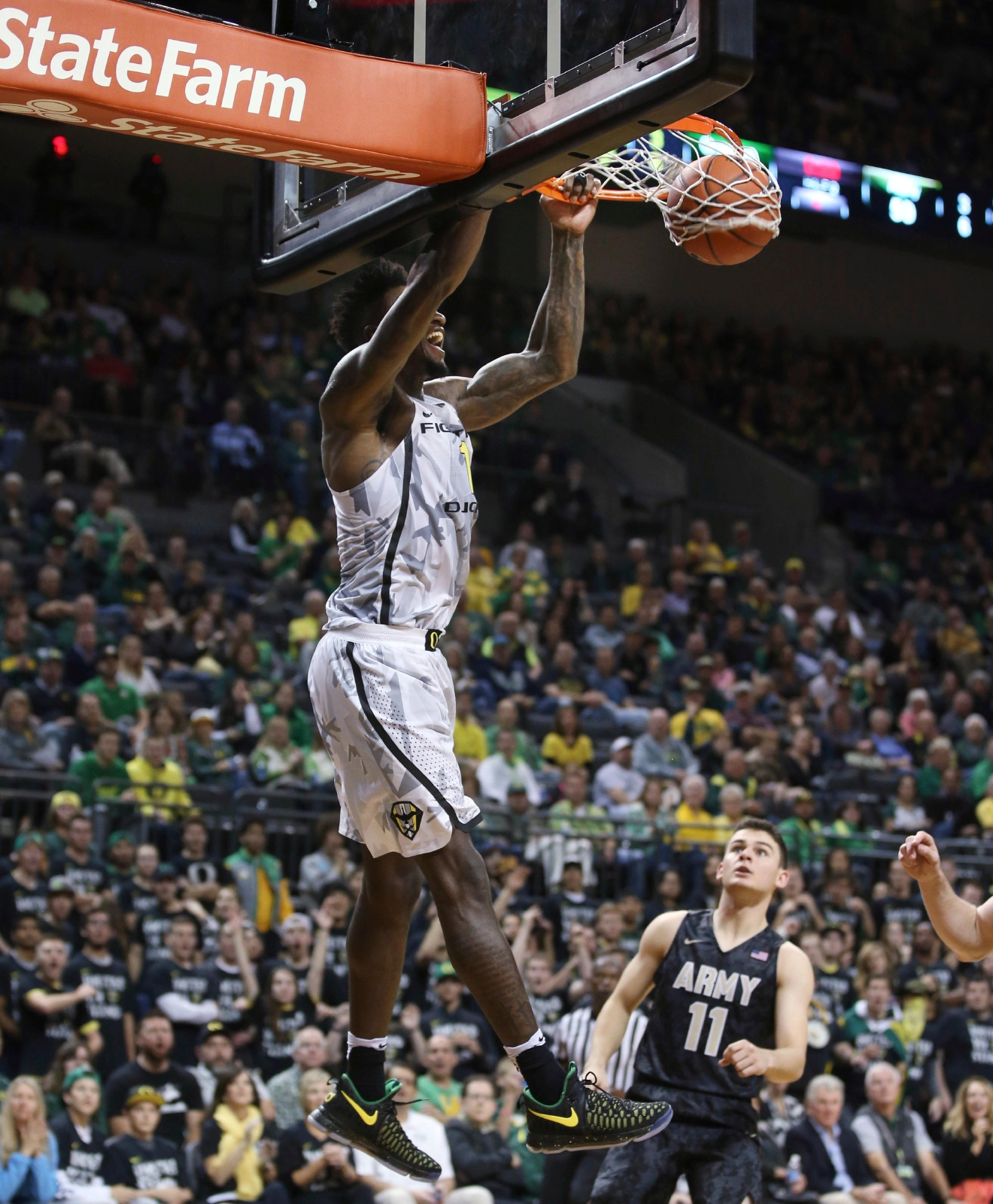 Oregon's Jordan Bell, left, dunks over Army's Thomas Funk during the second half of an NCAA college basketball game Friday, Nov. 11, 2016, in Eugene, Ore. (AP Photo/Chris Pietsch)