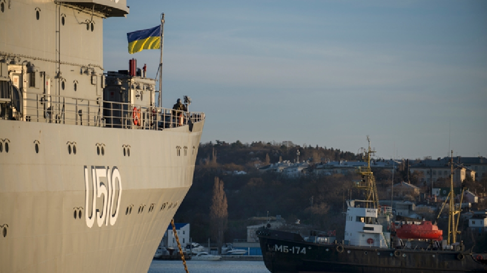 A Ukrainian national flag flies on the board of Ukrainian navy ship Slavutich at harbor of Sevastopol, Ukraine, Monday, March 3, 2014. The Ukrainian Defense Ministry said that Russian forces that have overtaken Ukraine's strategic region of Crimea are demanding that the ship's crew surrender. (AP Photo/Andrew Lubimov)