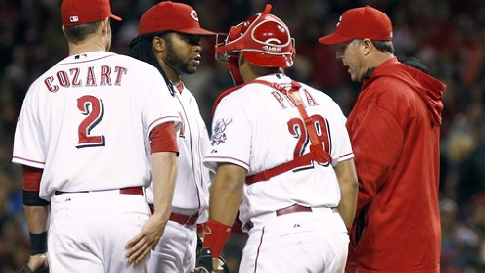 Cincinnati Reds manager Bryan Price, far right, talks with Cincinnati starting pitcher Johnny Cueto, second from left, shortstop Zack Cozart (2) and catcher Brayan Pena (29) in the eighth inning of a baseball game against the Milwaukee Brewers, Saturday, May 3, 2014, in Cincinnati. The Reds won 6-2. (AP Photo/David Kohl)