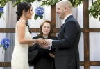 In this photo taken on Saturday, Aug. 23, 2014, and released by Hyatt Regency Boston, Boston Marathon bombing survivor, James Costello, right, marries Krista D'Agostino at the hotel in Boston. Officiating is Carol Merletti, center. The couple met at Spaulding Rehabilitation Hospital where D'Agostino worked as a nurse and helped Costello recover from his burns and injuries. (AP Photo/Prudente Photography)