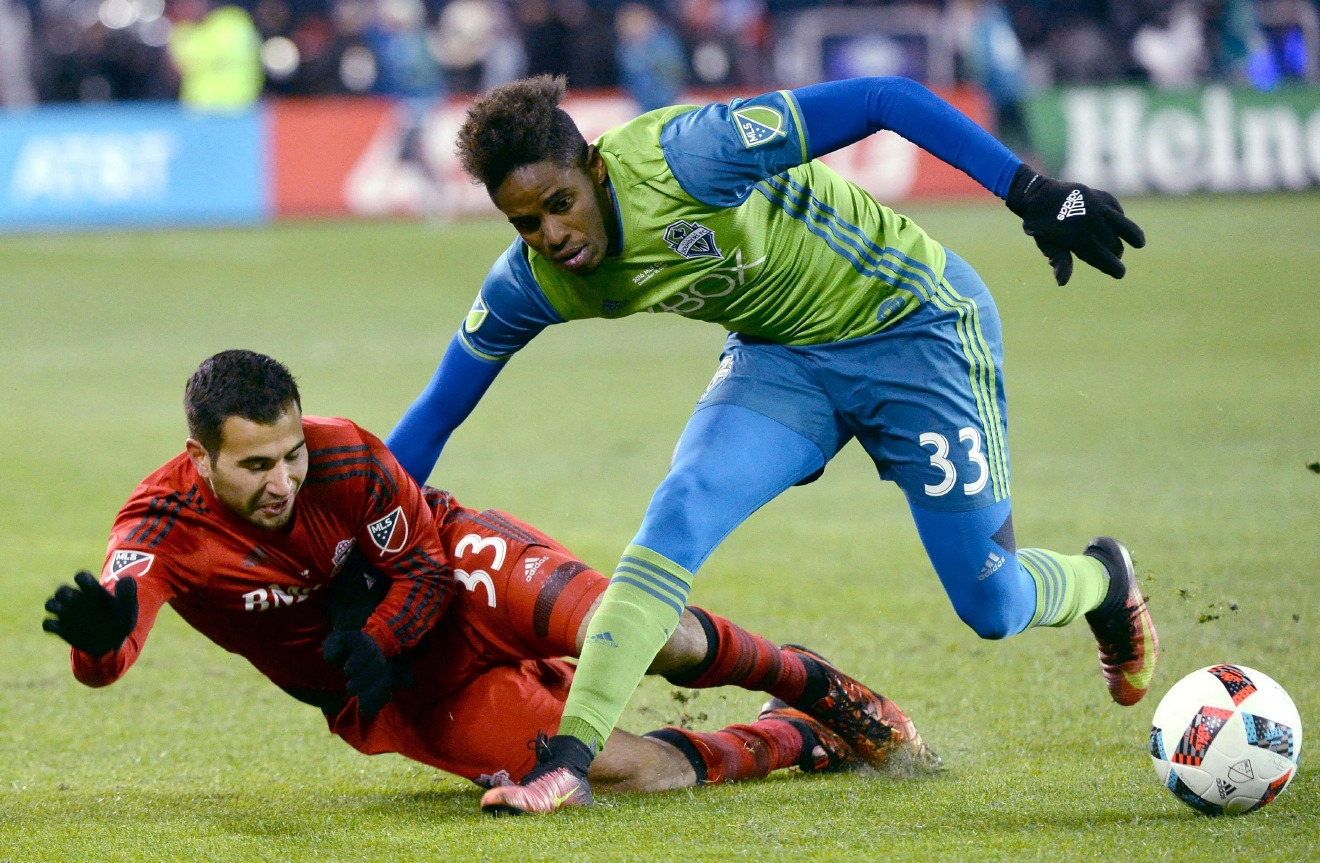 Seattle Sounders defender Joevin Jones (right) pushes down Toronto FC defender Steven Beitashour during second-half MLS Cup final soccer action in Toronto, Saturday, Dec. 10, 2016. (Nathan Denette/The Canadian Press via AP)