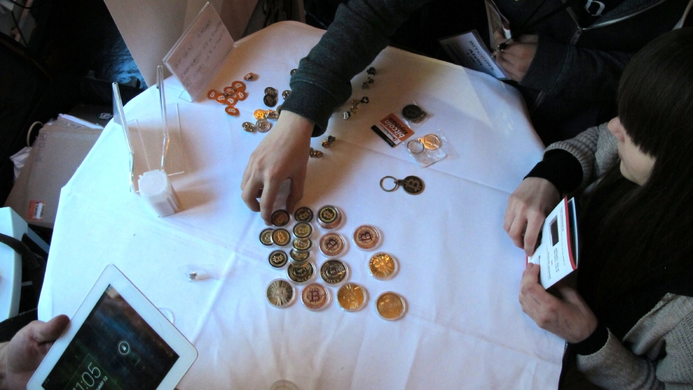 In this Feb. 12, 2014 file photo, attendees of the Inside Bitcoins conference in Berlin examine Bitcoin buttons. (AP Photo/Frank Jordans, File)