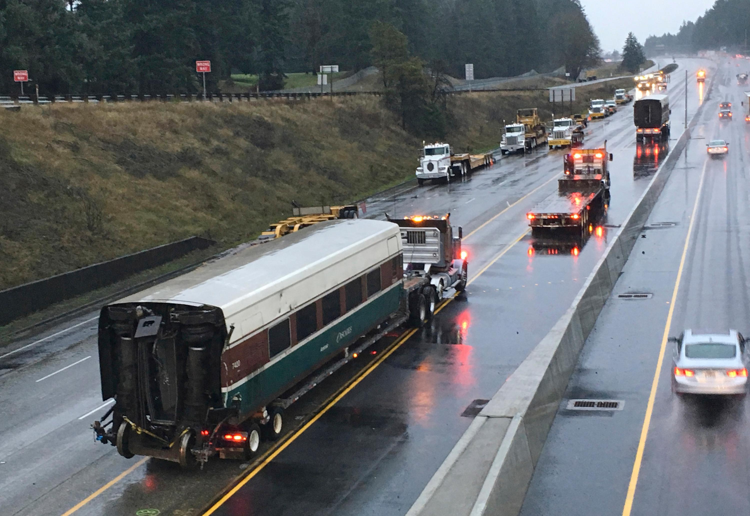 An Amtrak train car that careened off an overpass south of Seattle is hauled away on Interstate 5 Tuesday, Dec. 19, 2017, in Dupont, Wash.  Federal investigators say they don't yet know why the train was traveling 50 mph over the speed limit when it derailed Monday, killing some people and injuring dozens.  (AP Photo/Haven Daley)