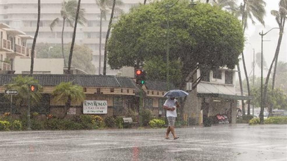 A man uses an umbrella against the rain as he walks across Kapiolani Blvd in Waikiki in Honolulu on Friday, Aug. 8, 2014. Rain and wind gusts are hitting parts of Oahu as Tropical Storm Iselle heads towards the island. Iselle is the first tropical storm to hit the state in 22 years. (AP Photo/Marco Garcia)