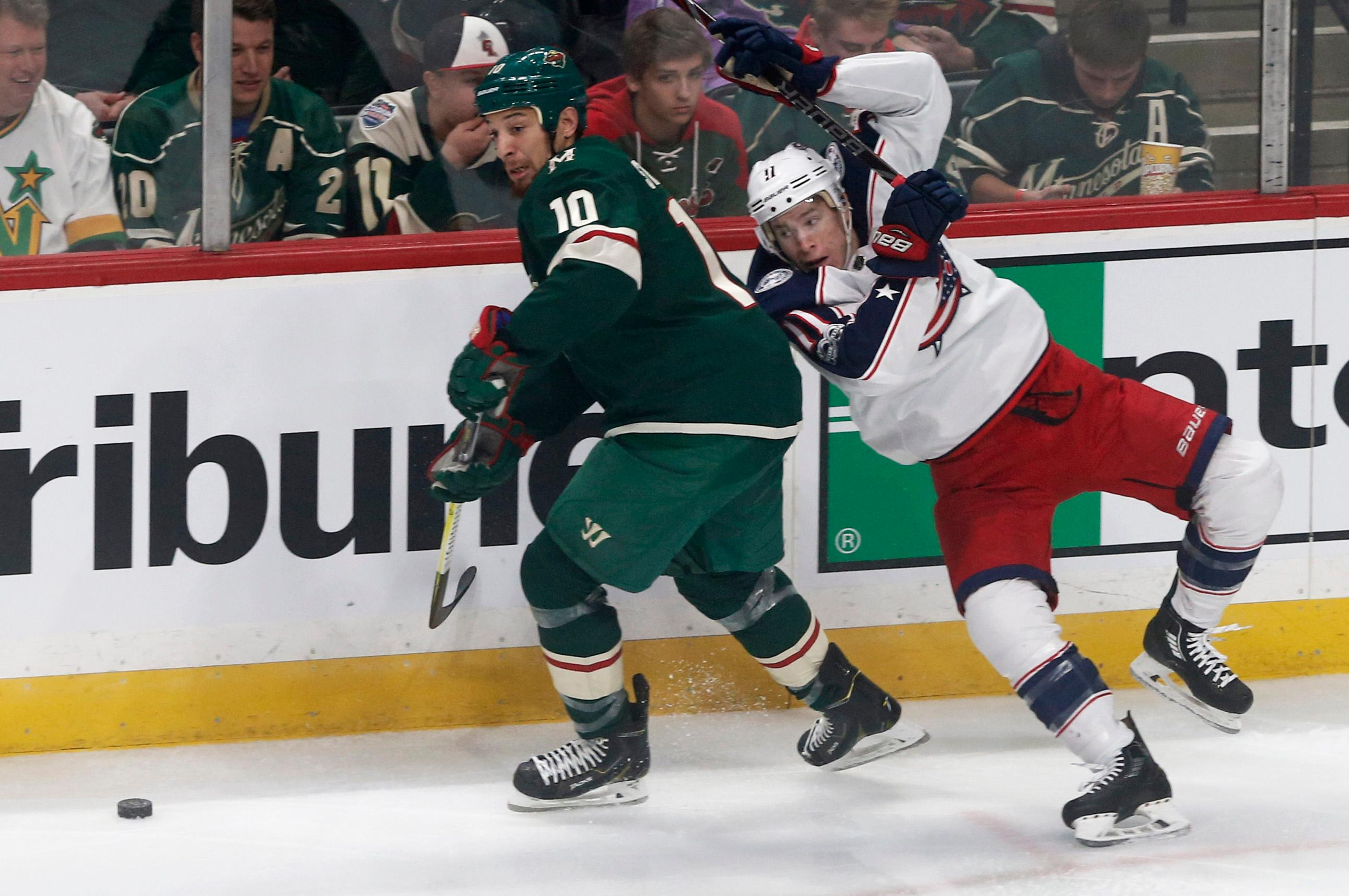 Columbus Blue Jackets' Matt Calvert, right, loses his balance as he and Minnesota Wild's Chris Stewart chase the puck during the first period of an NHL hockey game Saturday, Oct. 14, 2017, in St. Paul, Minn. (AP Photo/Jim Mone)