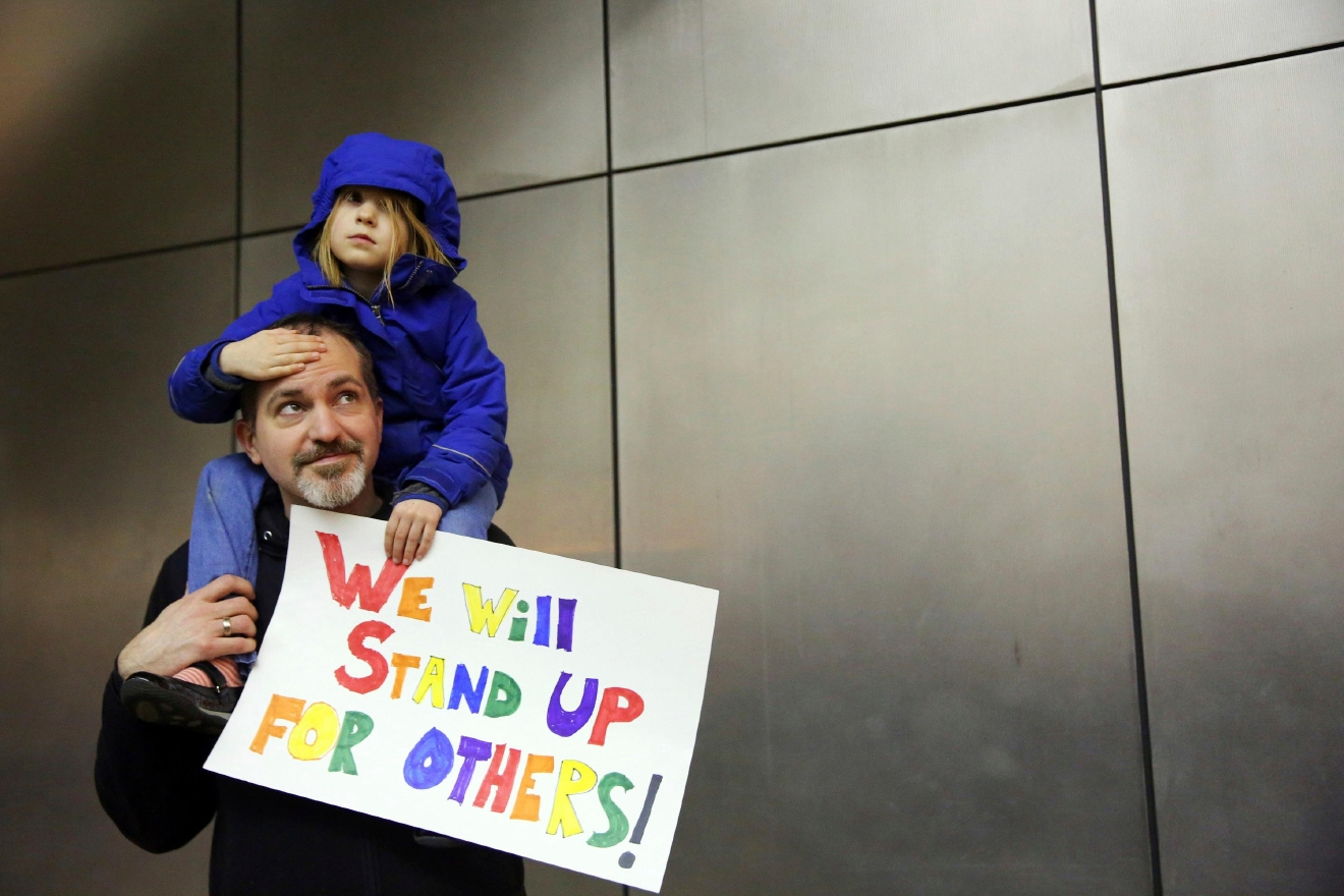 Matt Sernett holds his daughter Wade, 5, atop his shoulders, as more than 1,000 people gather at Seattle-Tacoma International Airport, to protest President Donald Trump's order that restricts immigration to the U.S., Saturday, Jan. 28, 2017, in Seattle. (Genna Martin/seattlepi.com via AP)