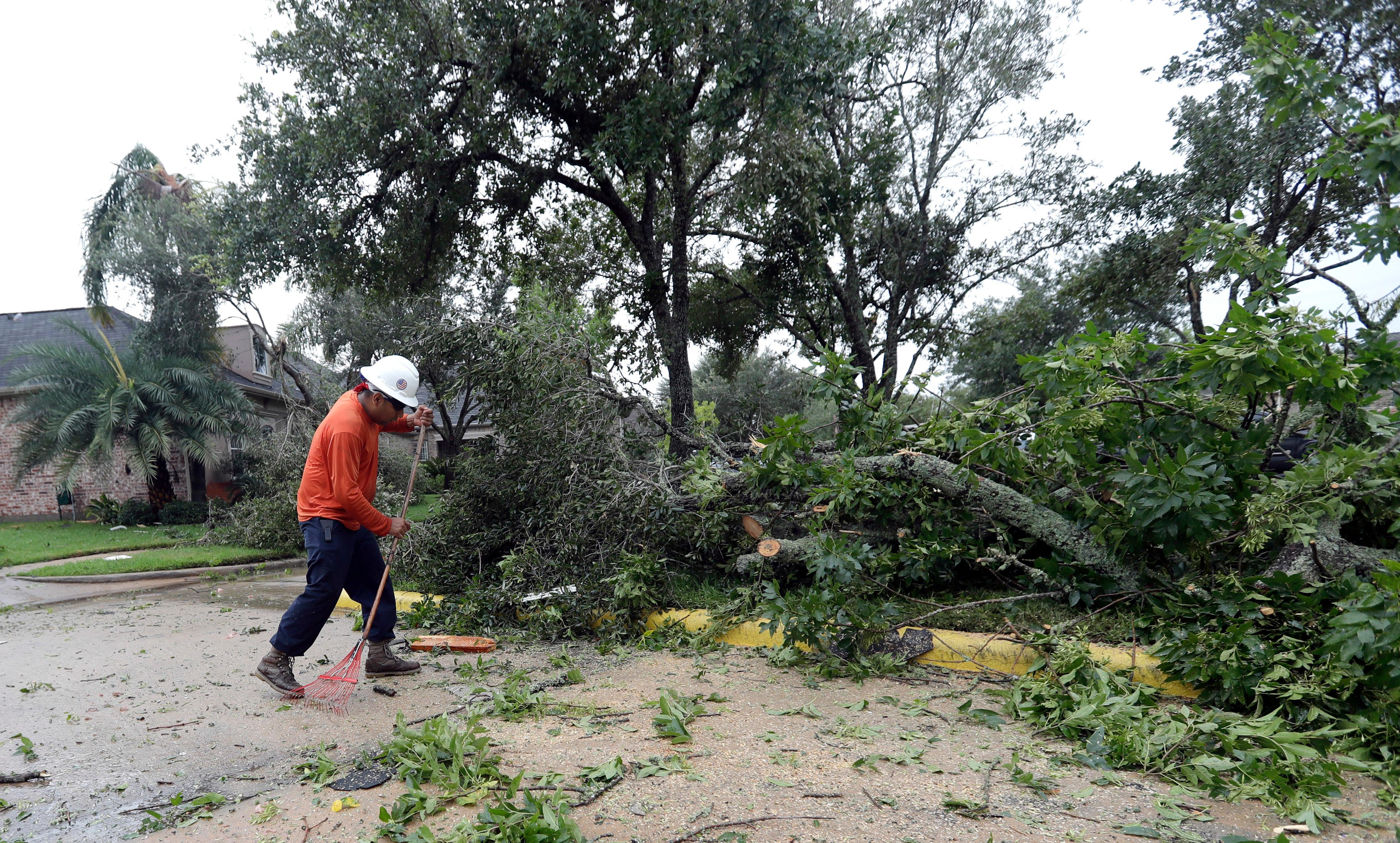 Abel Carreno cleans up after Hurricane Harvey Saturday, Aug. 26, 2017, in Missouri City, Texas.  Harvey rolled over the Texas Gulf Coast on Saturday, smashing homes and businesses and lashing the shore with wind and rain so intense that drivers were forced off the road because they could not see in front of them.  (AP Photo/David J. Phillip)