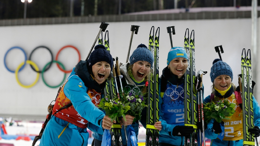 Ukraine's relay team Vita Semerenko, Juliya Dzhyma, Olena Pidhrushna and Valj Semerenko, from left, celebrate winning the gold during the flower ceremony of the women's biathlon 4x6k relay at the 2014 Winter Olympics, Friday, Feb. 21, 2014, in Krasnaya Polyana, Russia. (AP Photo/Kirsty Wigglesworth)