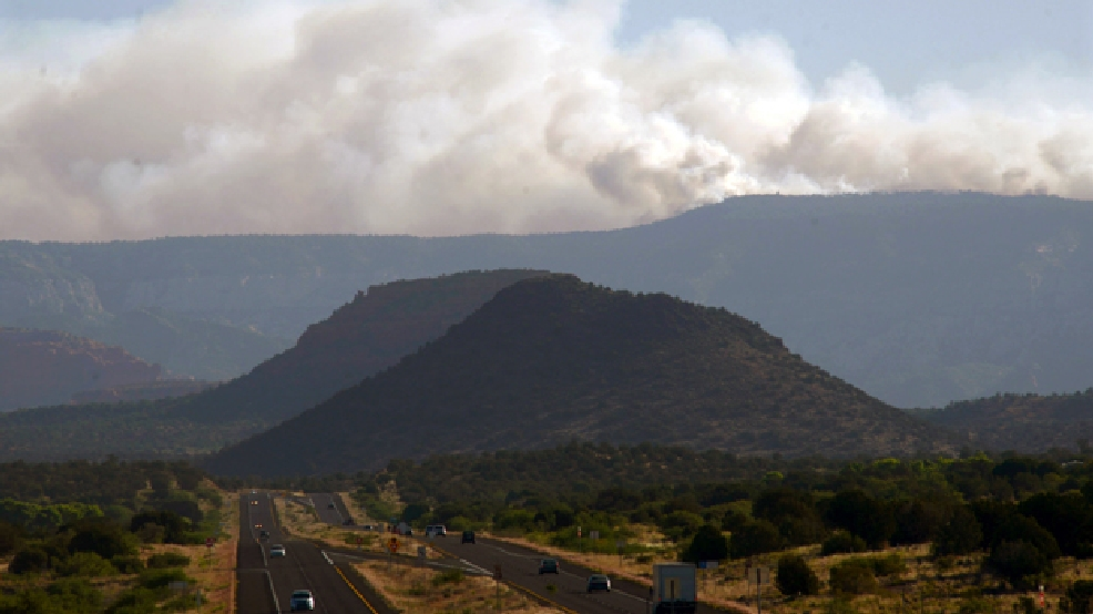 Plumes of smoke from a wildfire rise from Oak Creek Canyon in Sedona, Ariz., as seen from 89A near Sedona, Ariz., early Wednesday morning, May 21, 2014. About 200 firefighters and other personnel are already assigned to the 450-acre Slide Fire, including five Hotshot crews, Coconino National Forest officials said Wednesday. (AP Photo/Vyto Starinskas)