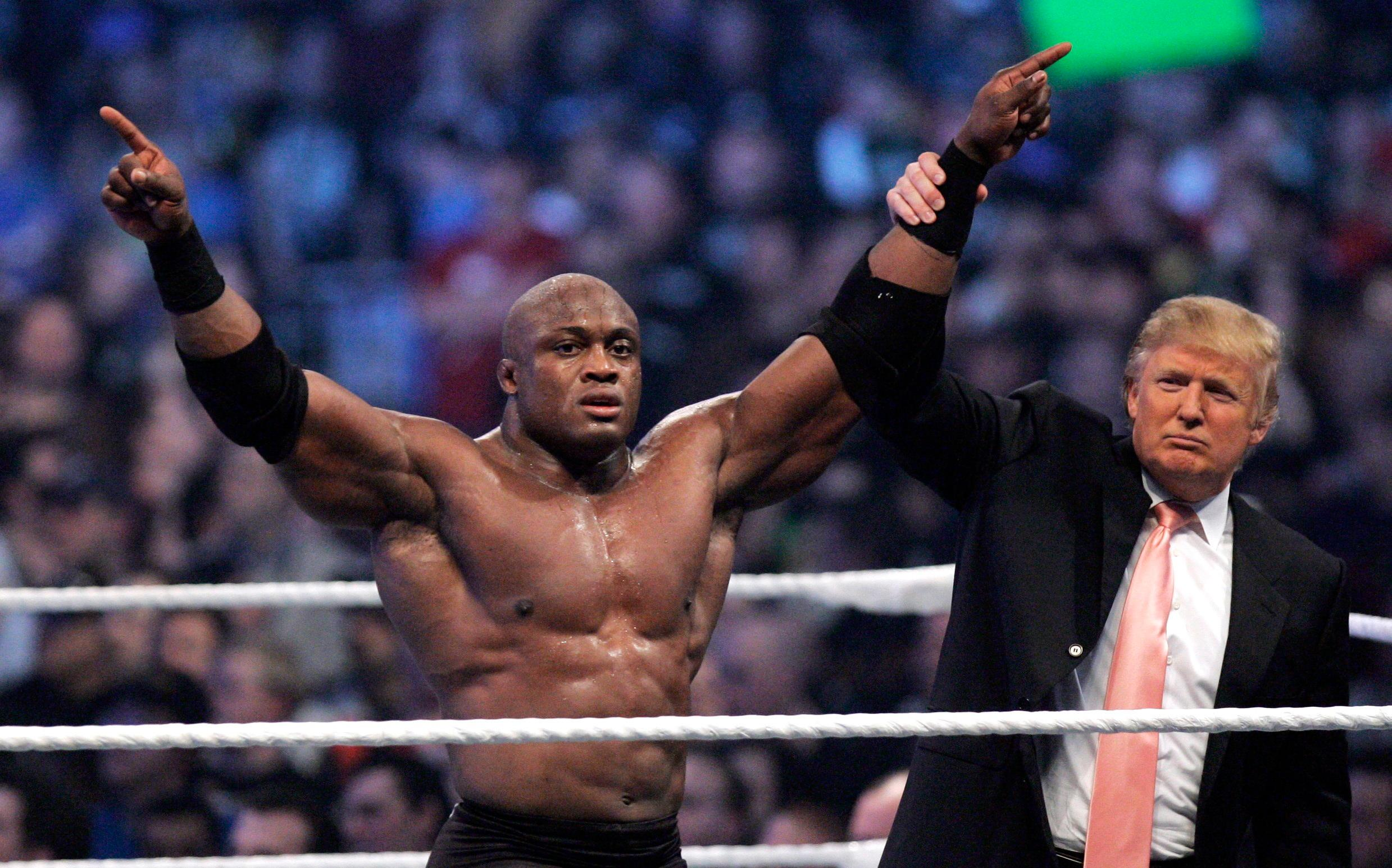 "FILE - In this Sunday, April 1, 2007, file photo, Donald Trump raises the arm of wrestler Bobby Lashley after he defeated Umaga at Wrestlemania 23 at Ford Field in Detroit. Trump body-slammed and then shaved the head of WWE boss Vince McMahon after what was known as the ""Battle of the Billionaires."" Wrestling aficionados say the president has, consciously or not, long borrowed the time-tested tactics of the game to cultivate the ultimate antihero character, a figure who wins at all costs, incites outrage and follows nobody's rules but his own. (AP Photo/Carlos Osorio, File)"