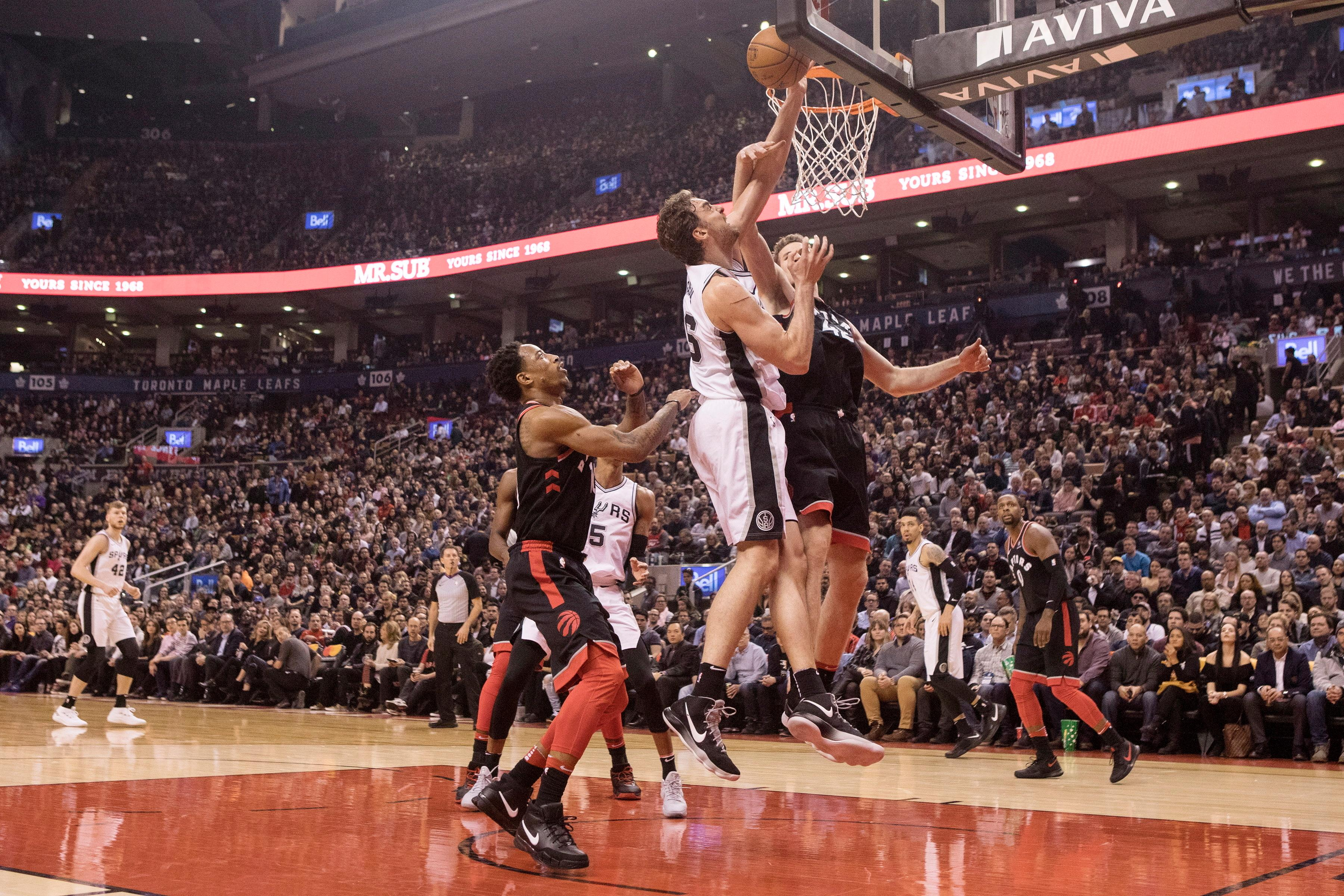 San Antonio Spurs center Pau Gasol (16) goes up for a shot as Toronto Raptors center Jakob Poeltl (42) defends during the first half of an NBA basketball game Friday, Jan. 19, 2018, in Toronto. (Chris Young/The Canadian Press via AP)