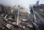 Firefighters battle a fire after a building collapse in the East Harlem neighborhood of New York, Wednesday, March 12, 2014. (AP Photo/John Minchillo)