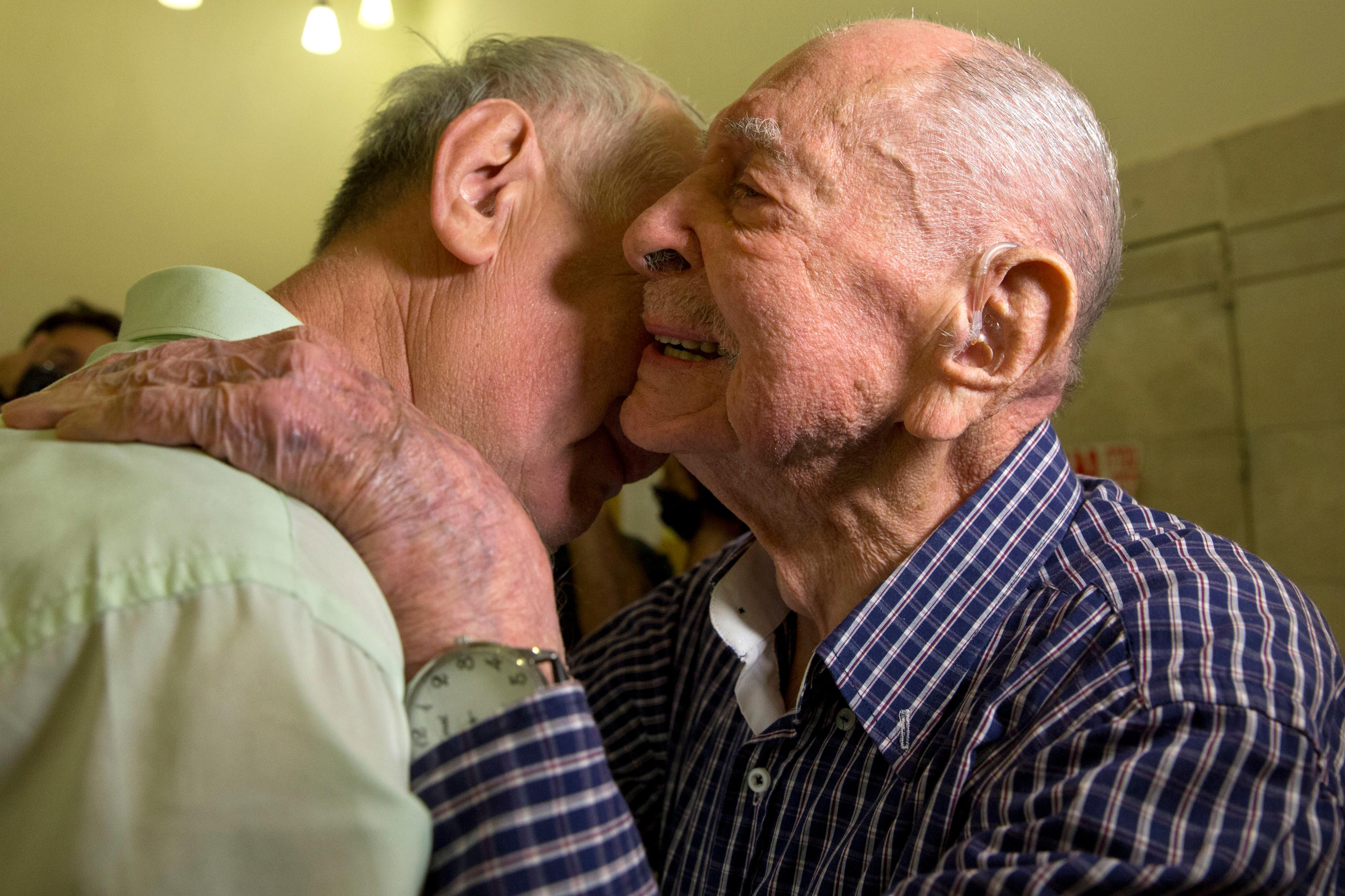 In this Thursday, Nov. 16, 2017 photo, Israeli Holocaust survivor Eliahu Pietruszka, right, embraces Alexandre Pietruszka as they meet for the first time in Kfar Saba. Pietruszka who fled Poland at the beginning of World War II and thought his entire family had perished learned that a younger brother had also survived, and his son, 66-year-old Alexandre, flew from Russia to see him. (AP Photo/Sebastian Scheiner)