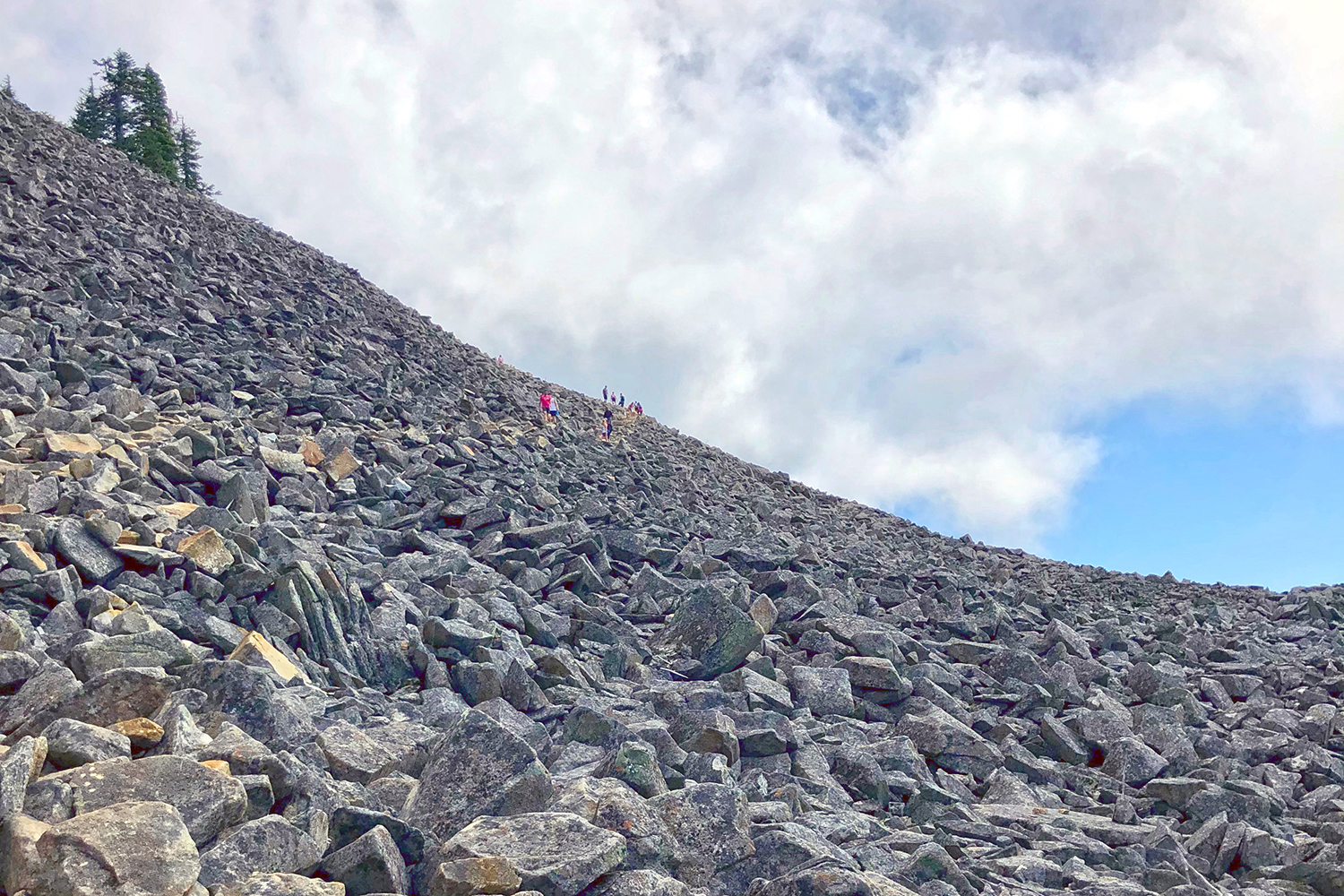 <p>The tree-covered trail suddenly opens up to blue skies and a massive boulder field. At first sight, it's hard to determine just how large – but look close and spot a few people making their way to the top (Image:{&nbsp;}Rachael A. Jones / Seattle Refined){&nbsp;}</p>