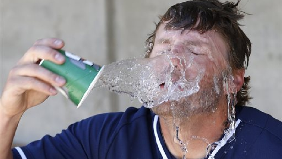 Milwaukee Brewers' Mark Reynolds splashes water on his face in the dugout prior to a spring training baseball game against the Texas Rangers, Tuesday, March 18, 2014, in Phoenix. (AP Photo/Ross D. Franklin)