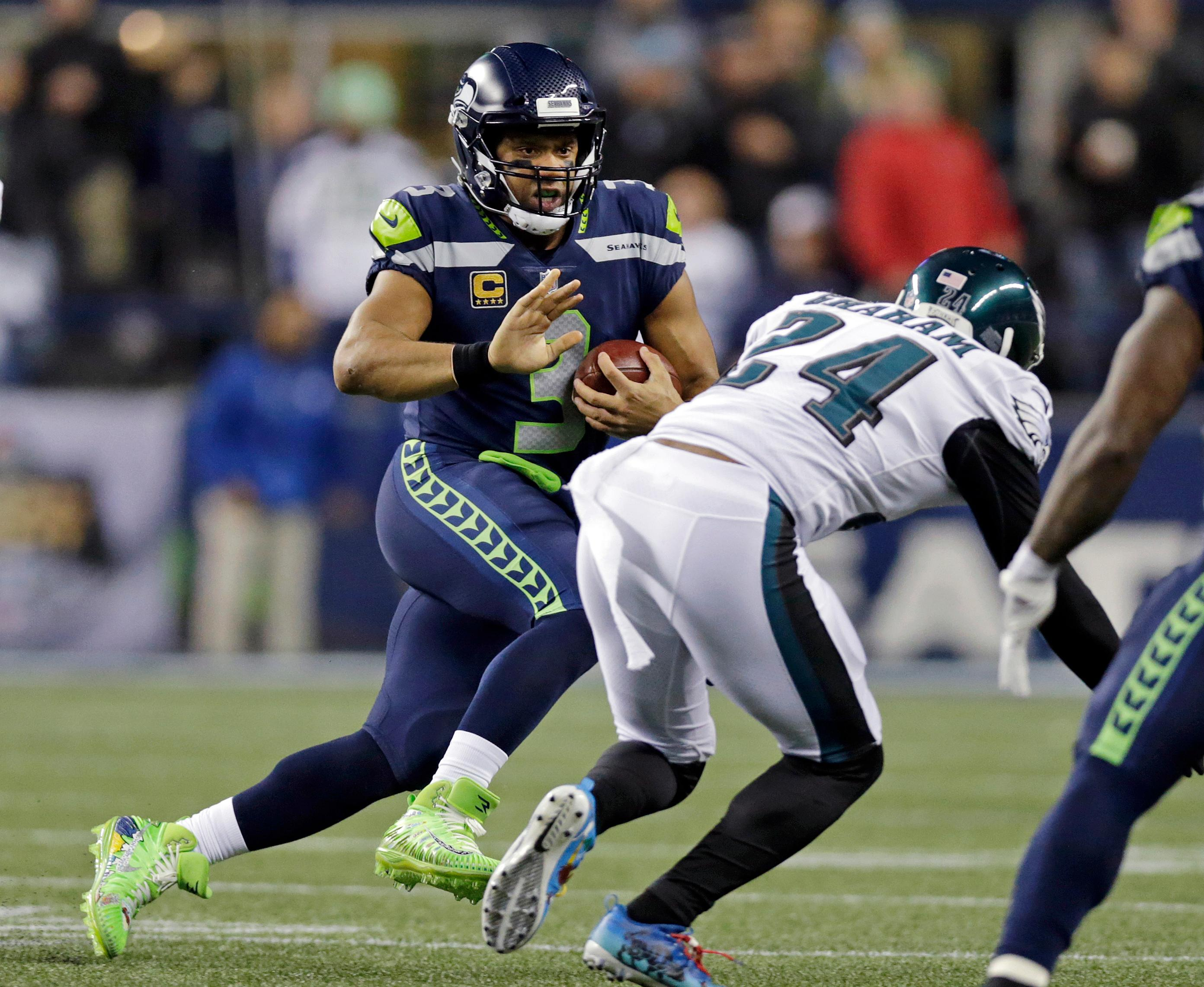 Seattle Seahawks quarterback Russell Wilson, left, scrambles as Philadelphia Eagles' Corey Graham (24) moves in during the first half of an NFL football game, Sunday, Dec. 3, 2017, in Seattle. (AP Photo/John Froschauer)