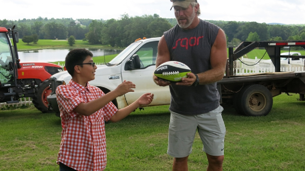 Retired NFL quarterback Brett Favre gives some passing pointers to Roque Dunagan, 11, on Monday, June 9, 2014 at the farm of actress Sela Ward in Lauderdale County, Miss. (AP Photo/The Meridan Star, Terri Ferguson Smith )