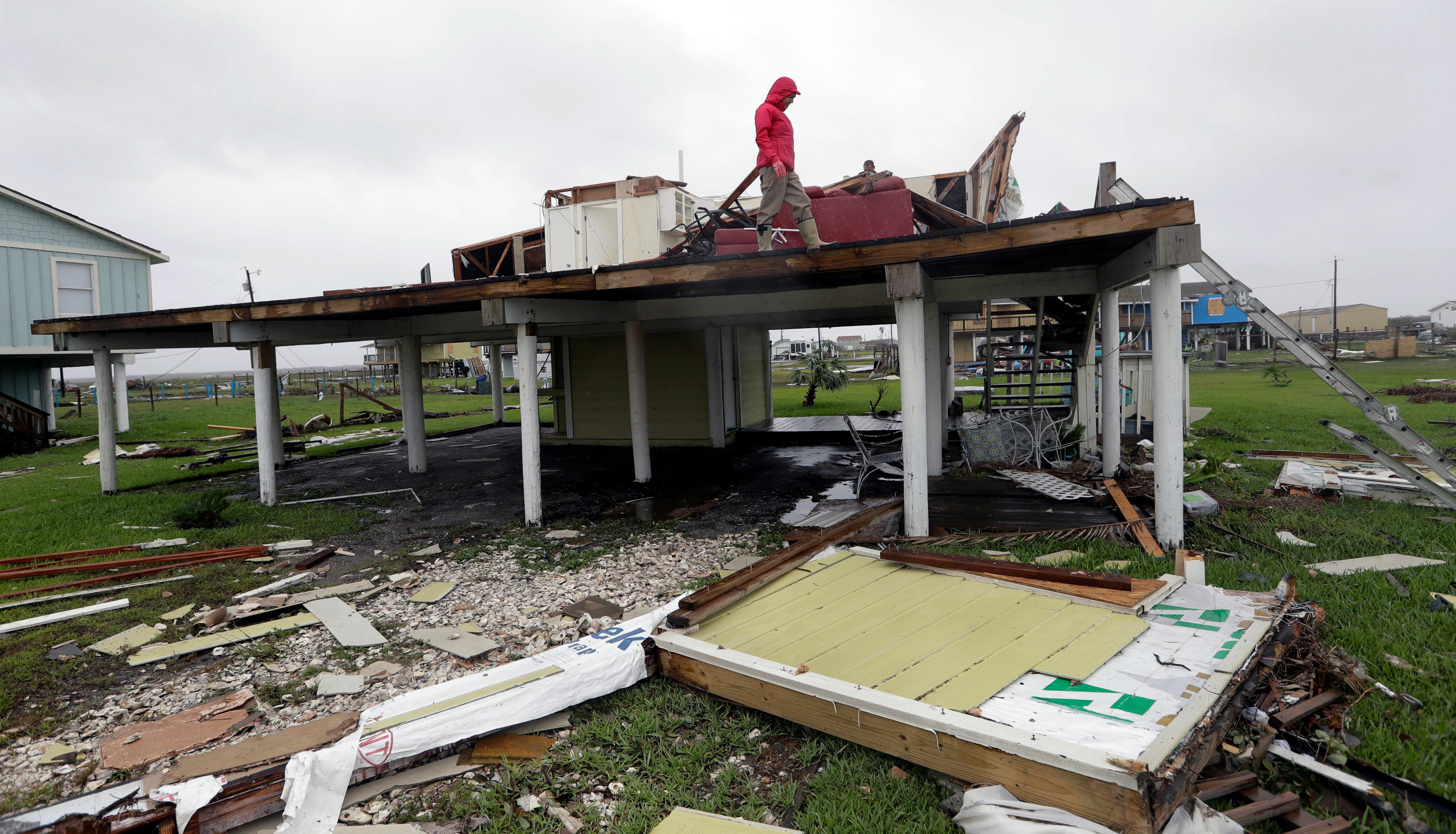 Evelyn Perkins inspects her home which was destroyed in the wake of Hurricane Harvey, Monday, Aug. 28, 2017, in Rockport, Texas. (AP Photo/Eric Gay)