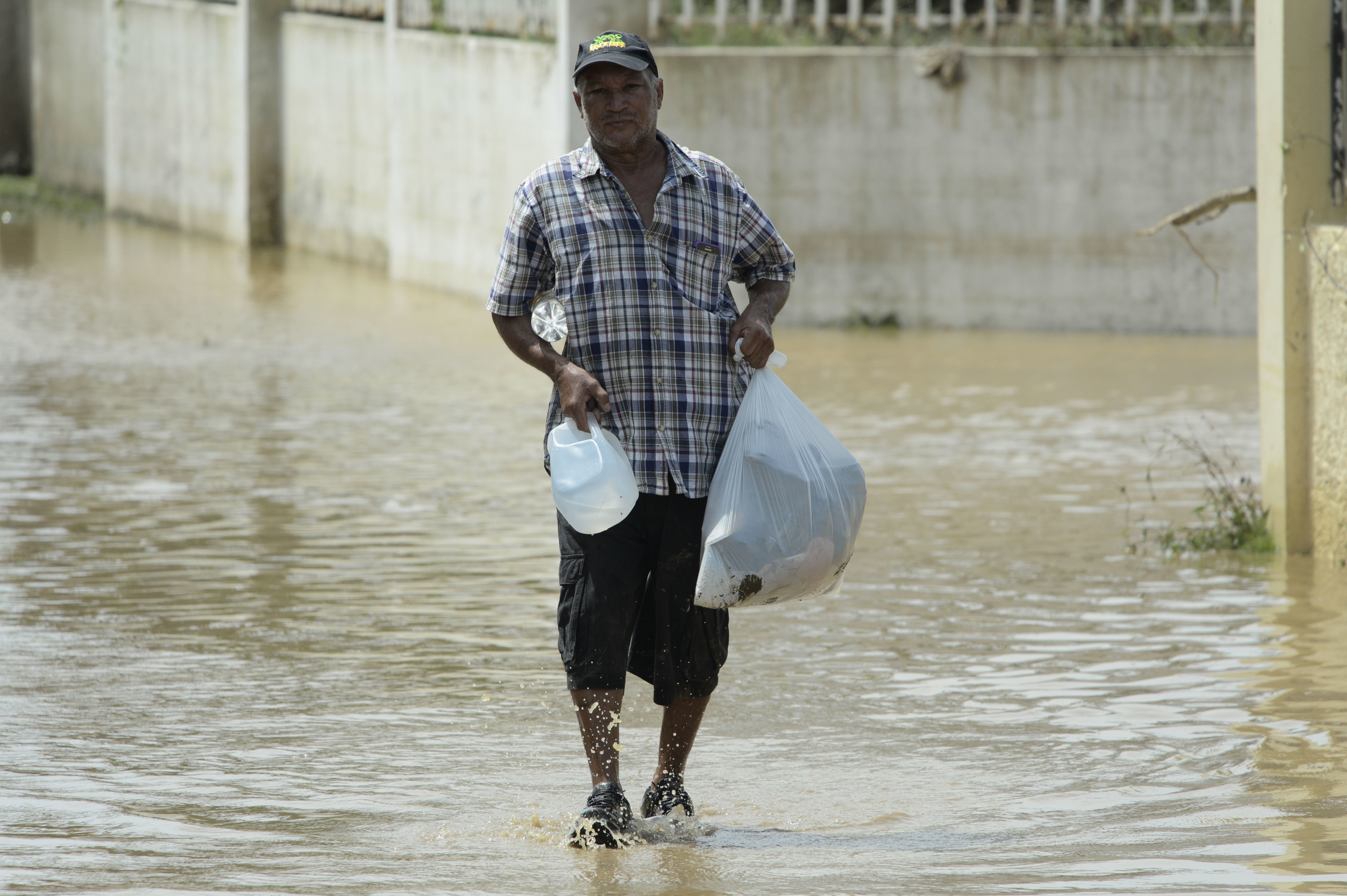 A resident carries supplies in a flooded road after the passing of Hurricane Maria, in Toa Baja, Puerto Rico, Friday, September 22, 2017. Because of the heavy rains brought by Maria, thousands of people were evacuated from Toa Baja after the municipal government opened the gates of the Rio La Plata Dam. (AP Photo/Carlos Giusti)
