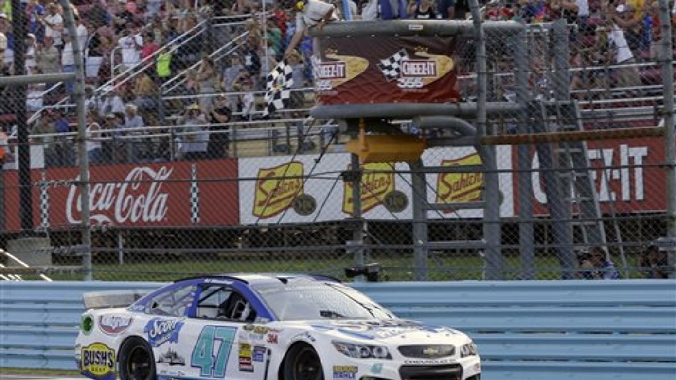 AJ Allmendinger (47) takes the checkered flag to win a NASCAR Sprint Cup Series auto race at Watkins Glen International, Sunday, Aug. 10, 2014, in Watkins Glen N.Y. (AP Photo/Derik Hamilton)