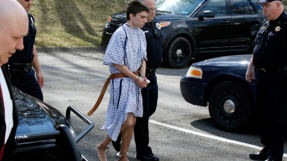 Alex Hribal, the suspect in the multiple stabbings at the Franklin Regional High School in Murrysville, Pa., is escorted by police to a district magistrate to be arraigned on Wednesday, April 9, 2014, in Export, Pa. Authorities say Hribal has been charged after allegedly stabbing and slashing at least 19 people including students in the crowded halls of his suburban Pittsburgh high school Wednesday. (AP Photo/Keith Srakocic)
