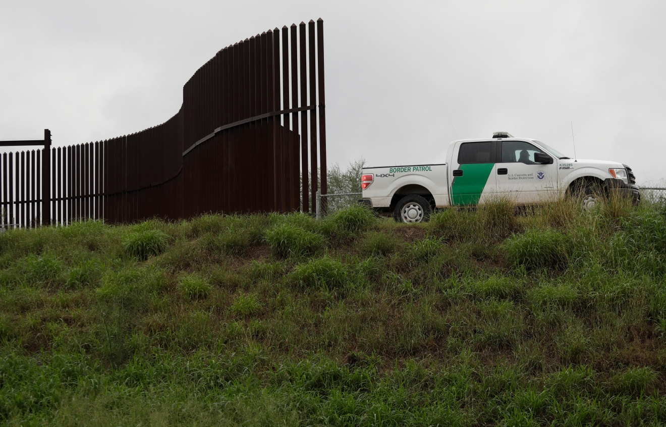 "FILE - This Nov. 13, 2016, file photo shows a U.S. Customs and Border Patrol agent passes along a section of border wall in Hidalgo, Texas. President Donald Trump will face many obstacles in building his ""big, beautiful wall"" on the U.S.-Mexico border, including how to pay for it and how to contend with unfavorable geography and the legal battles ahead.  (AP Photo/Eric Gay, File)"