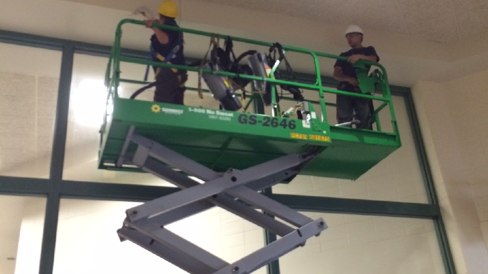 Workers clean Preble High School after fire damage.