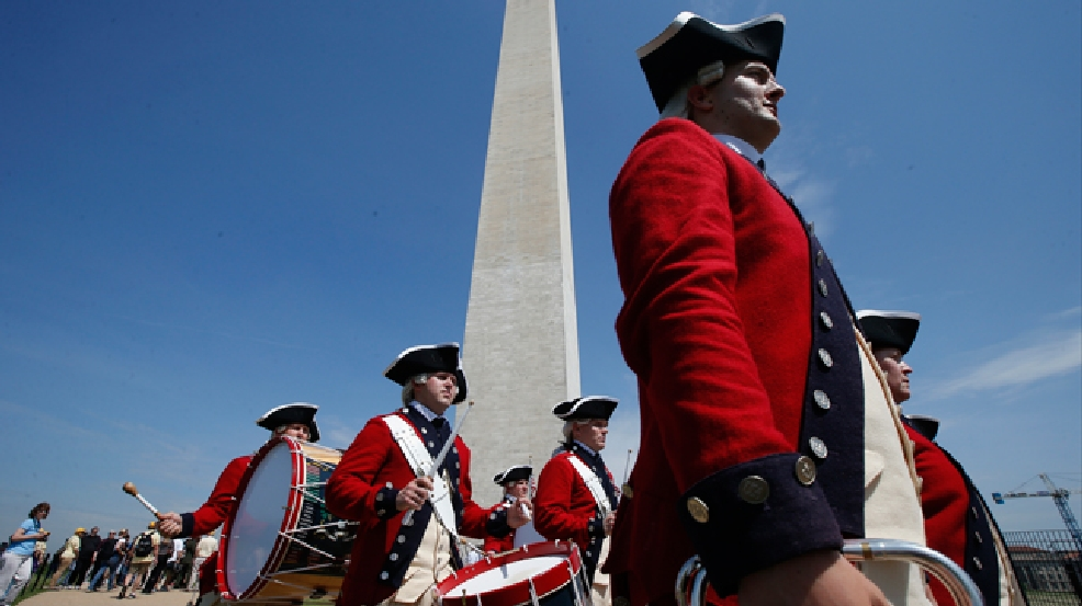 Members of the United States Army Old Guard Fife and Drums Corps march beneath the Washington Monument in Washington, Monday, May 12, 2014, during a ceremony to celebrate its re-opening. The monument, which sustained damage from an earthquake in August 2011, is now open to the public. (AP Photo)