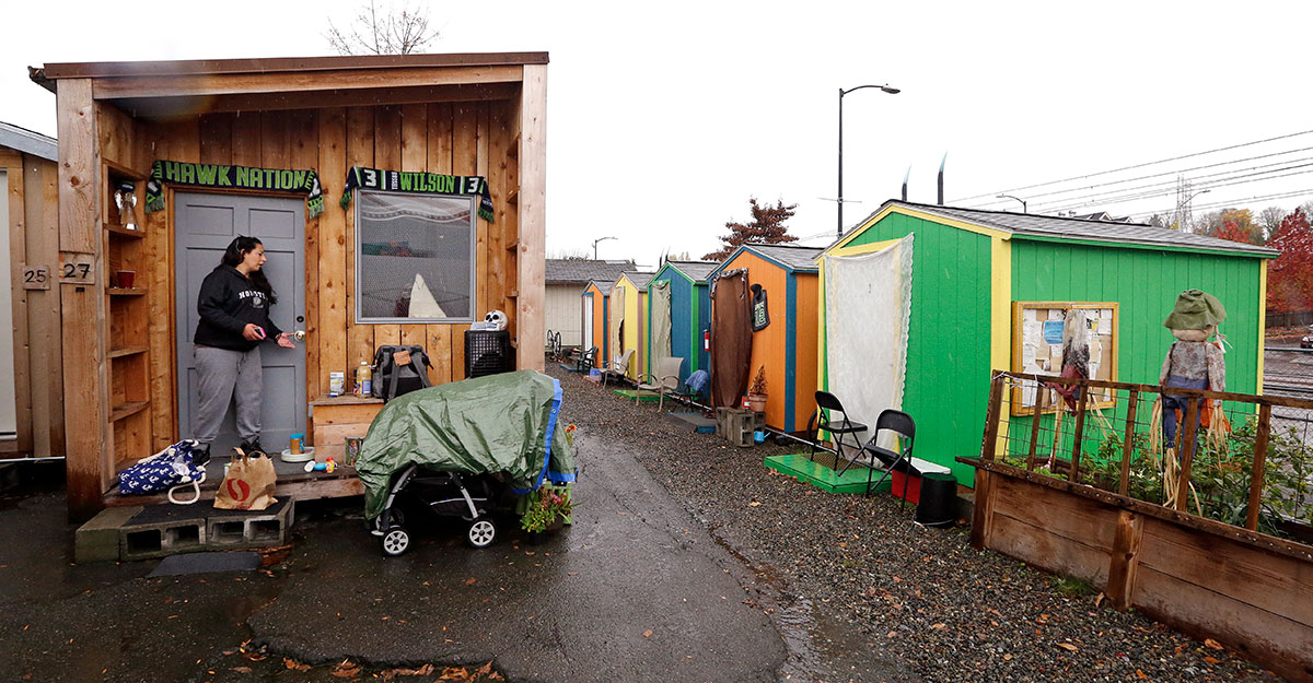 In this Nov. 9, 2017, file photo, Eva Stough opens the door to her tiny house, where she lives with her partner and baby, at a homeless encampment in Seattle. In the absence of legislation to incentivize the acceptance of Section 8 vouchers, politicians and advocates have been scrambling to keep up with the surge of unsheltered residents in the state. One answer in Seattle has been the so-called tiny houses, portable 120-square-foot shacks of simple wood construction, which now include seven villages with a capacity to house 350 people since its start in 2015. (AP Photo/Elaine Thompson, File)180306_ap_homeless_aid_AP18065039386909.jpg