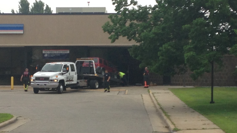 Oshkosh officials use a tow truck to haul a SUV out of the city's main post office after the vehicle crashed into it Sunday, July 6, 2014. (WLUK/Chris Bourassa)