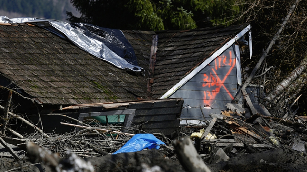 The orange X on a house, destroyed in the mud, indicates it has been searched for people on Highway 530, Sunday, March 23, 2014 the day after a giant landslide occurred near Oso, Wash. Rescue crews searched into the night for survivors from a massive mudslide that killed at least three people, after hearing voices from the debris field pleading for help. (AP Photo/The Seattle Times, Lindsey Wasson, Pool)