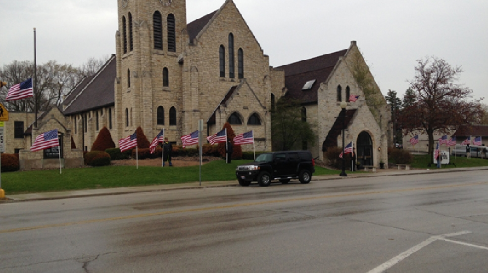 Flags fly in honor of Sgt. Heidi Ruh outside of St. Peter's Church of Christ in Kiel, Monday, May 19, 2014. (WLUK/Chris Bourassa)
