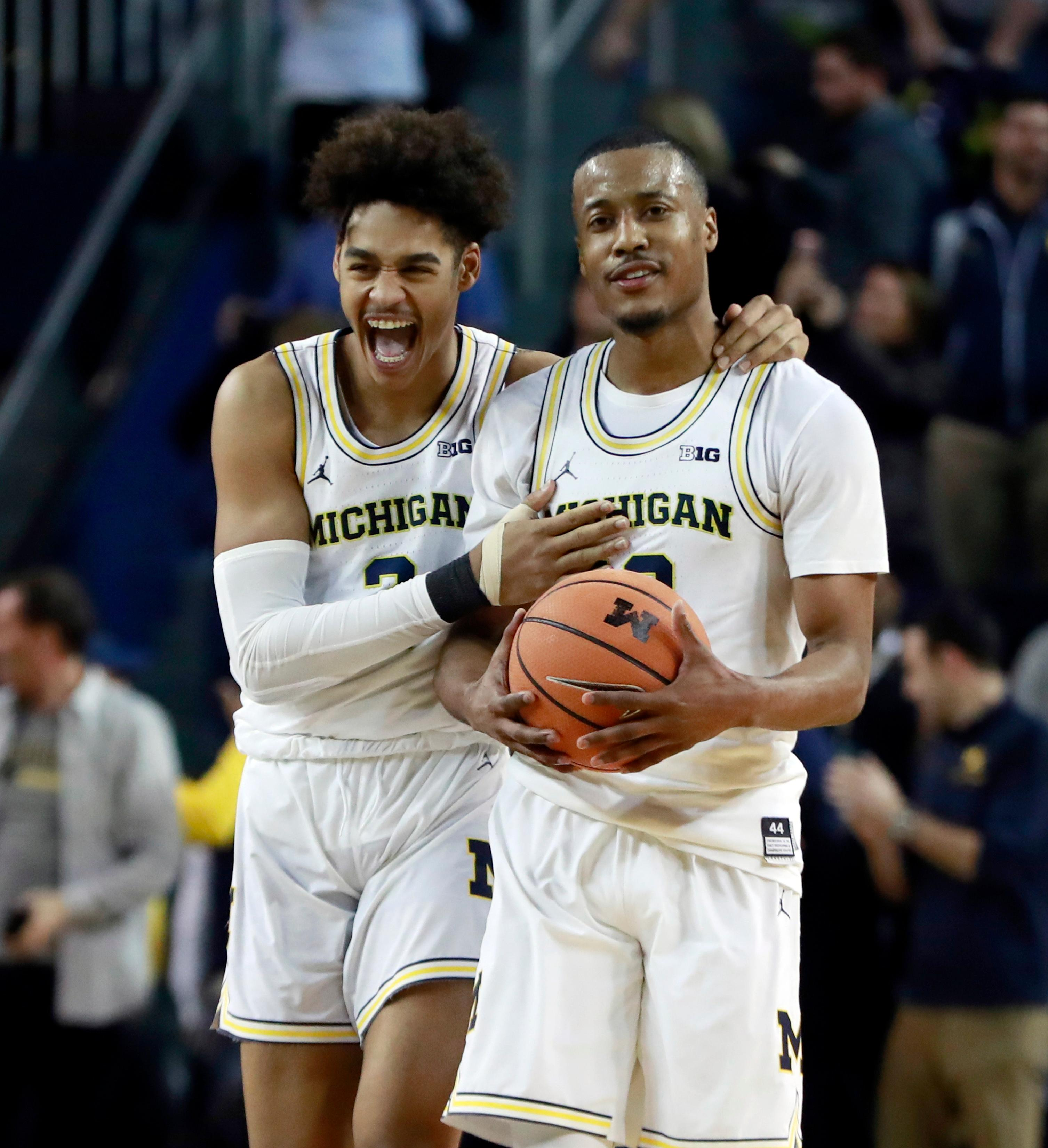 Michigan guard Jordan Poole, left, walks off the court with guard Muhammad-Ali Abdur-Rahkman after the team's 76-73 overtime win over Minnesota in an NCAA college basketball game, Saturday, Feb. 3, 2018, in Ann Arbor, Mich. (AP Photo/Carlos Osorio)