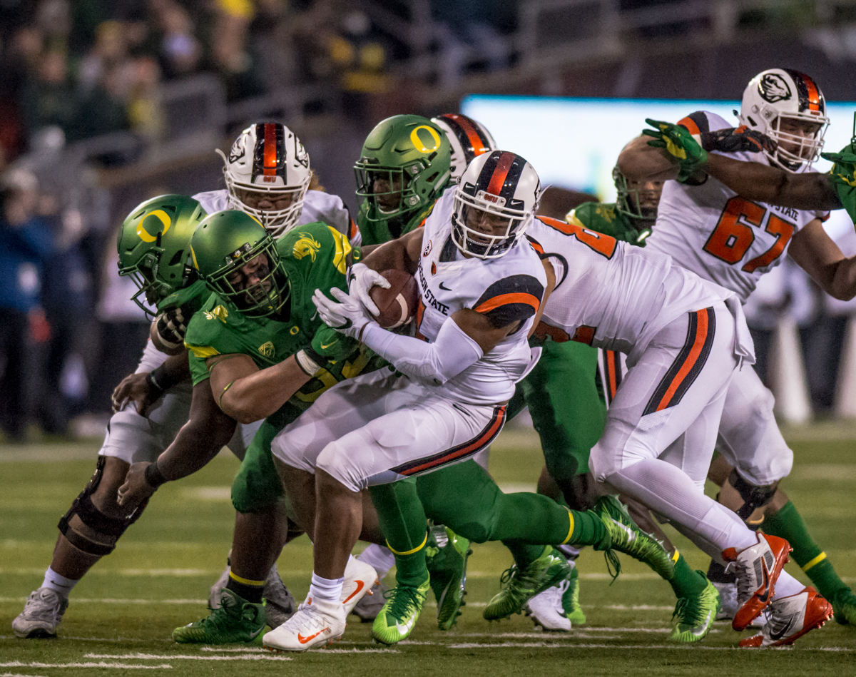 Oregon State running back Thomas Tyner (#4) is taken down by an Oregon defensive player. The Oregon Ducks defeated the Oregon State Beavers 69 to 10 in the 121st Civil War game at Autzen Stadium in Eugene, Ore. on Saturday November 25, 2017. Photo by Ben Lonergan, Oregon News Lab
