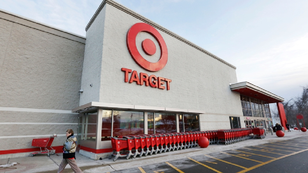 FILE - In this Dec. 19, 2013, file photo, a passer-by walks near an entrance to a Target retail store in Watertown, Mass. (AP Photo/Steven Senne, File)