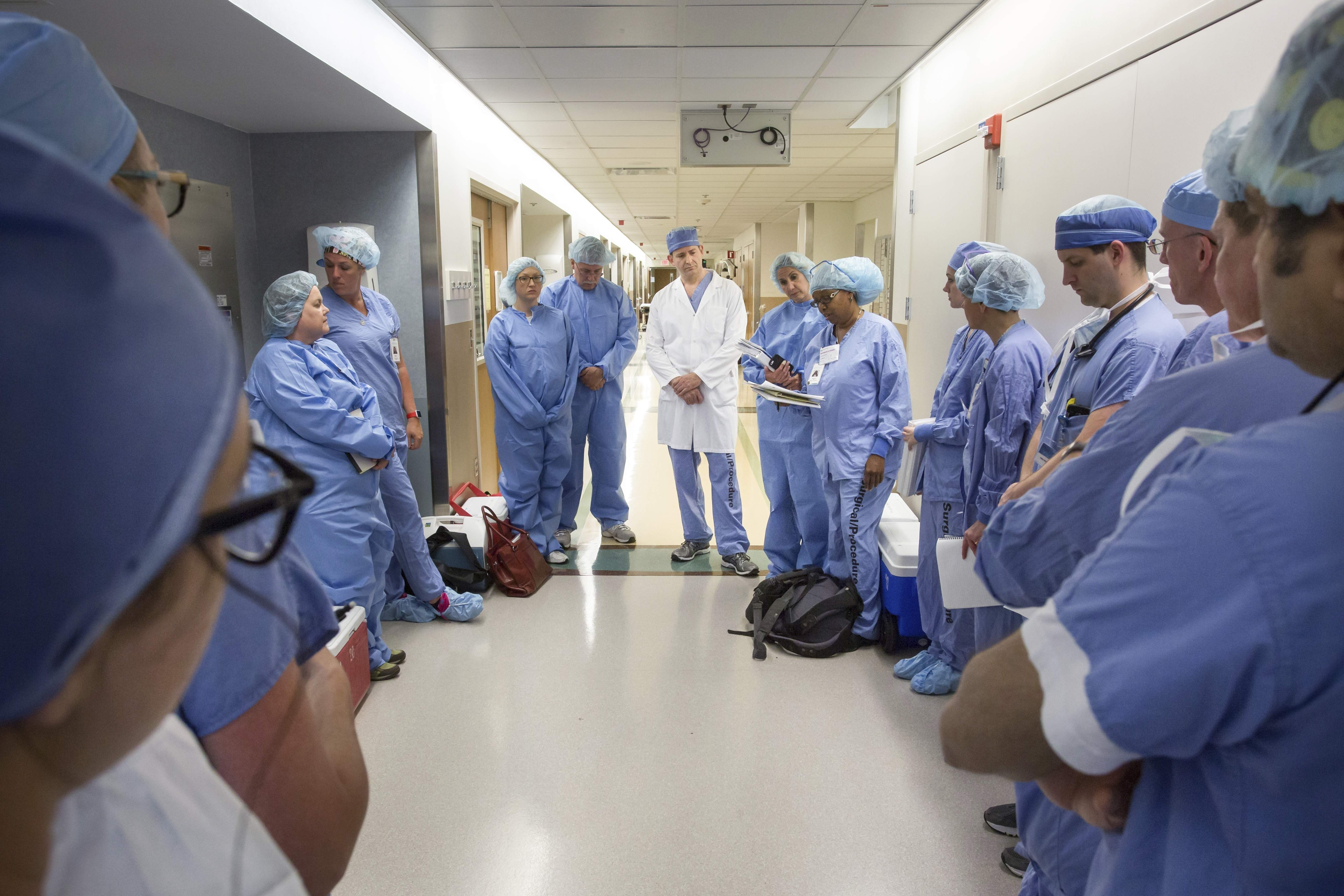 In this June 10, 2016, photo provided by the Mayo Clinic, a medical team of about 60 doctors, nurses, anesthesiologists and others at Mayo Clinic gather before performing the first face transplant surgery at their hospital in Rochester, Minn. Mardini and his team devoted more than 50 Saturdays over 3 1/2 years to rehearsing the procedure, using sets of cadaver heads to transplant the face of one to another. They used 3D imaging and virtual surgery to plot out the bony cuts so the donor's face would fit perfectly on Andy Sandness. THE ASSOCIATED PRESS