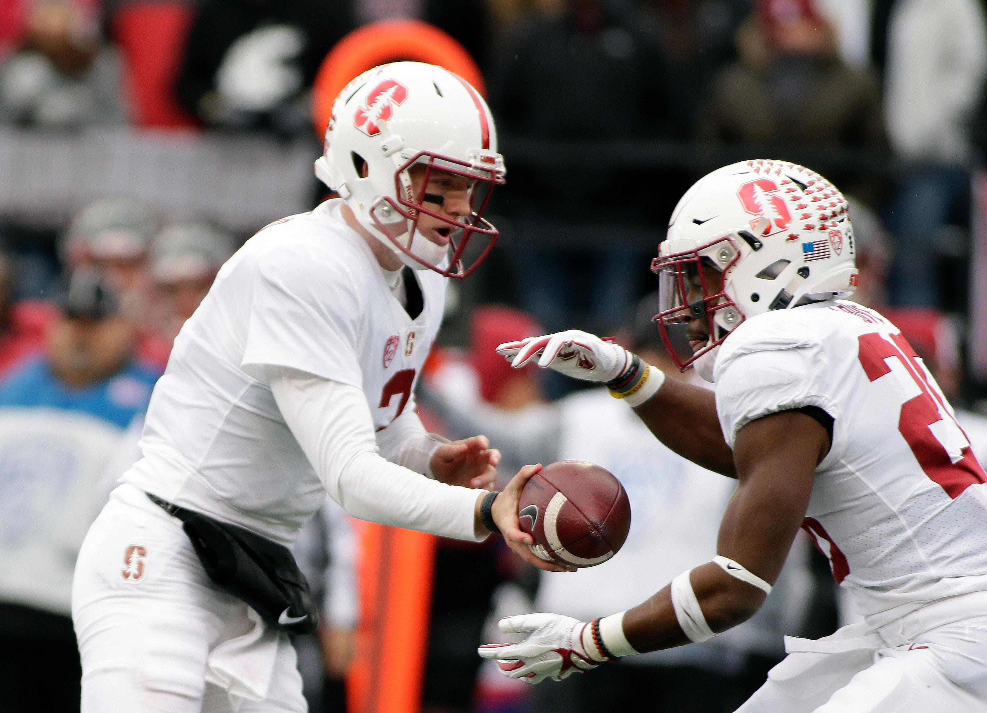 Stanford quarterback K.J. Costello, left, hands the ball off to running back Bryce Love during the first half of an NCAA college football game against Washington State in Pullman, Wash., Saturday, Nov. 4, 2017. (AP Photo/Young Kwak)