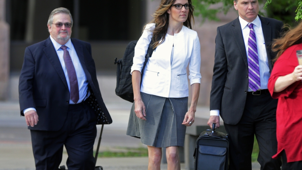 Taya Kyle, the widow of former Navy SEAL Chris Kyle, arrives with her attorneys at the federal courthouse Tuesday, July 8, 2014 in St. Paul, Minn., for the start of a trial in a lawsuit filed by former Minnesota Gov. Jesse Ventura against the Kyle estate. Ventura filed the defamation lawsuit claiming that Chris Kyle's account of a bar fight in a book he wrote was false. (AP Photo/Jim Mone)