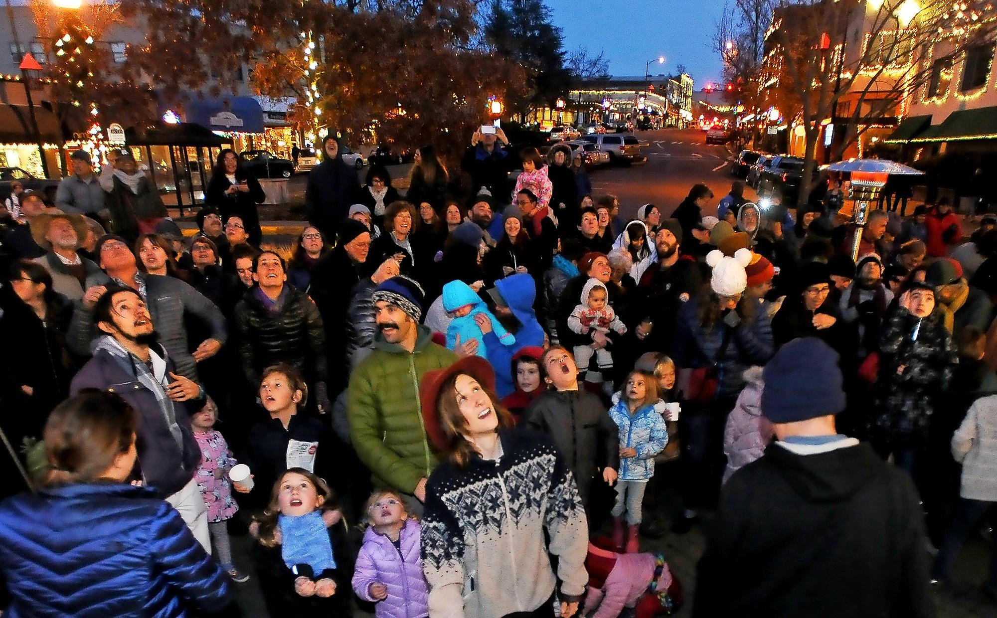 A crowd waits for chocolate coins to drop from a bucket truck during the annual menorah lighting Sunday on the Ashland Plaza. Photo by Denise Baratta