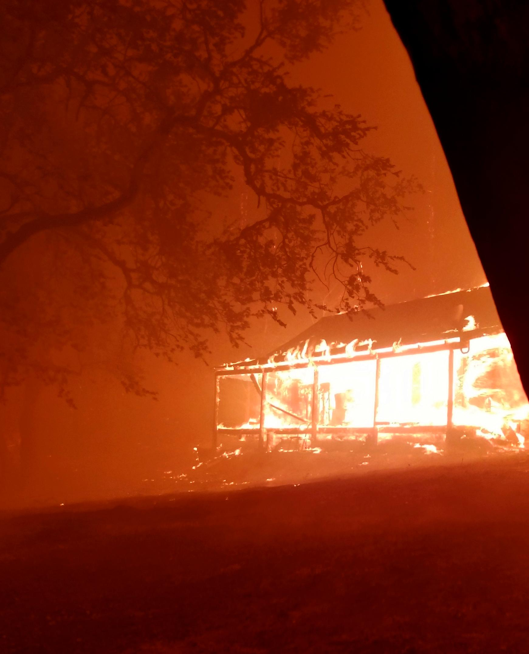 This Monday, Oct. 9, 2017, photo provided by Paul Hanssen shows his house burning in the Redwood Valley, Calif. Hanssen hid inside a portable trailer wrapped in water-soaked towels while the fast-moving wildfire tore through his mountain home. (Paul Hanssen via AP)