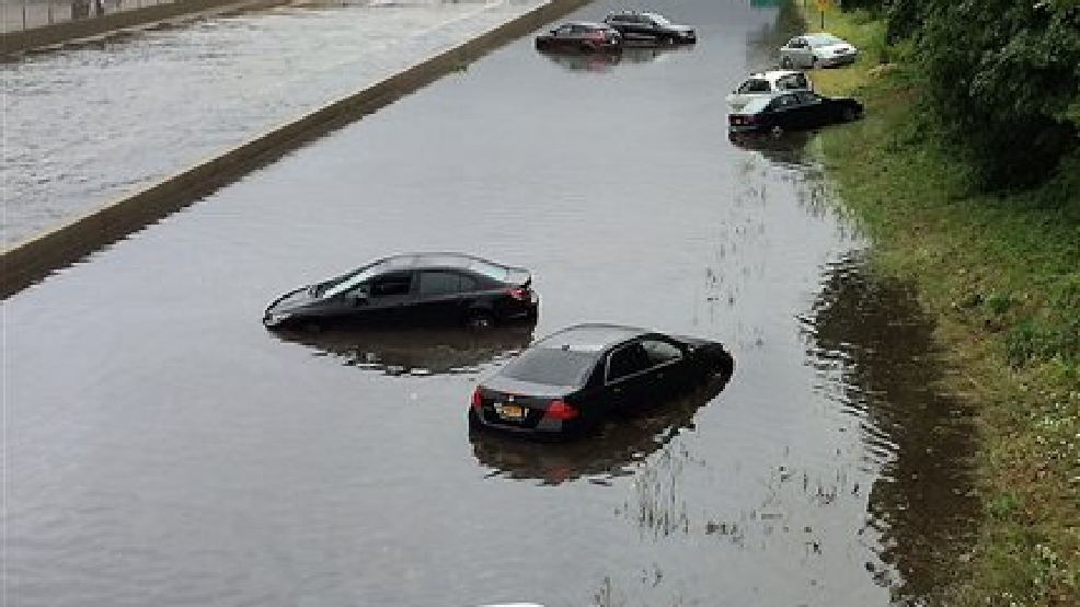 Vehicles are submerged on a flooded section of Sunrise Highway, in East Islip, N.Y., on New York's Long Island, Wednesday Aug. 13, 2014. Stranded Long Island drivers have been rescued after a storm slammed Islip, N.Y., with over 12 inches of rain — an entire summer's worth. (AP Photo/Ed Betz, Newsday)