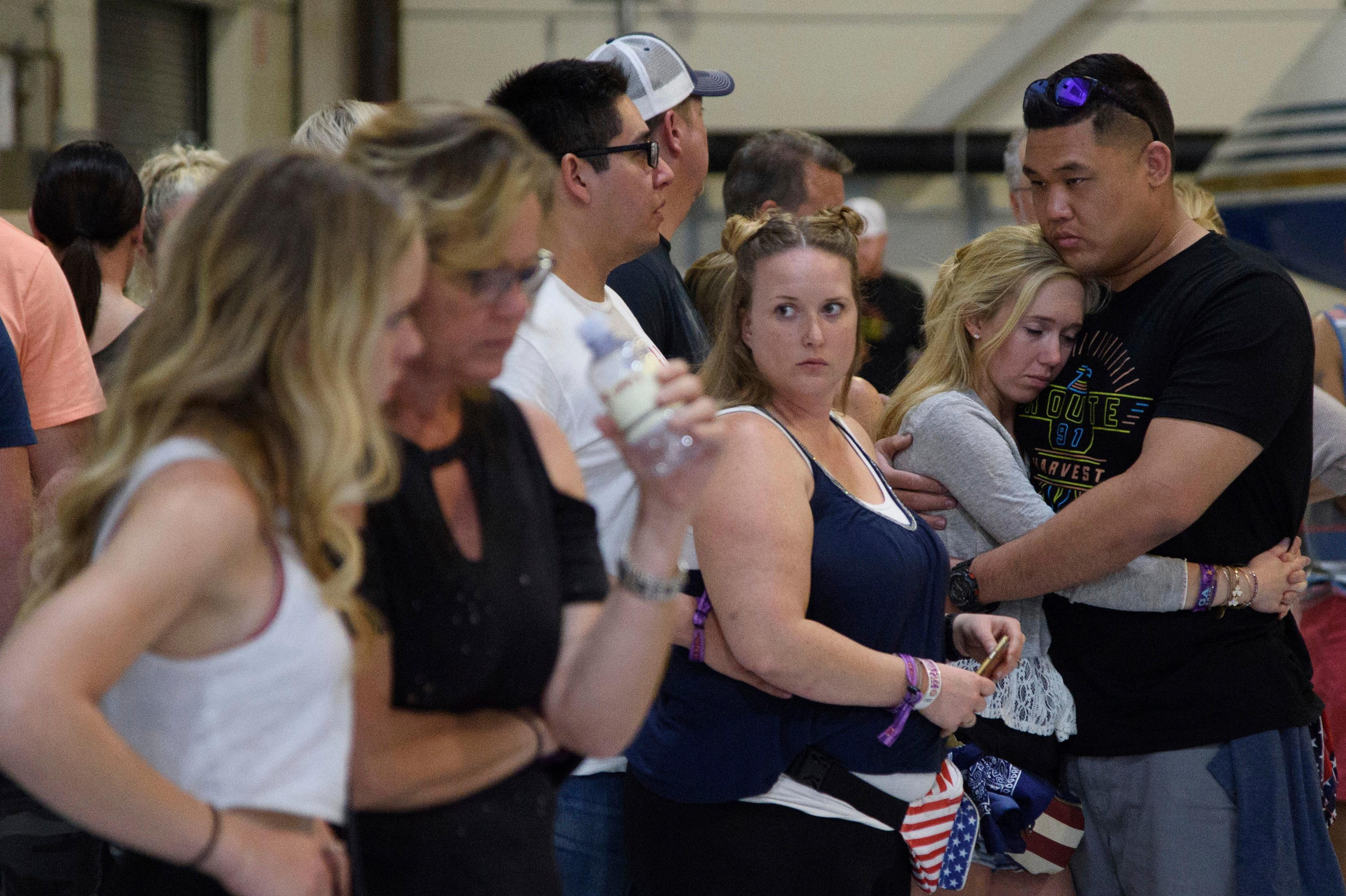 Concertgoers embrace as they wait early Monday, Oct. 2, 2017, inside the Sands Corporation plane hangar after a mass shooting in which dozens were killed  at the Route 91 Harvest country festival early Sunday. (Al Powers/Invision/AP)